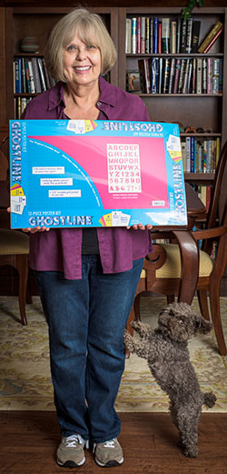 Mary Russell Sarao holds a package of Ghostline poster board. Photo by Michael Samples.
