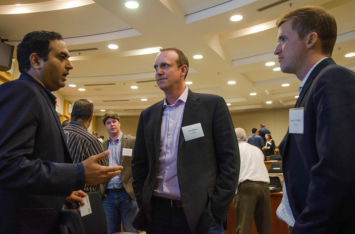 Audience members Brandon O'Halloran (right) and Josh Manley (middle) ask speaker Ray Bajaj about business between panels. Photo by Hannah Ridings.