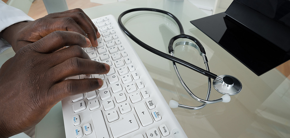 Close-up Of Male Doctor Hands Typing On Computer Keyboard At Desk
